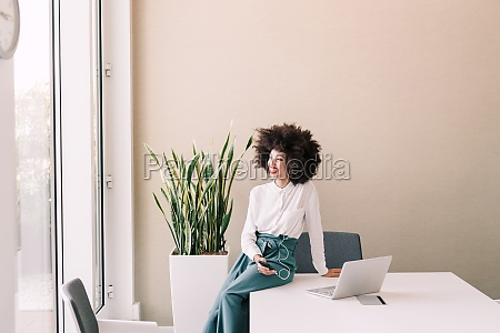 businesswoman on phone in office smiling