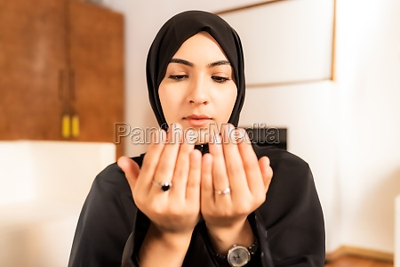 young muslim woman with hands together