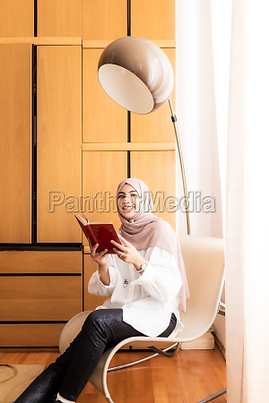 young muslim woman reading book