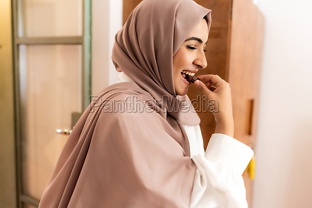 young muslim woman eating date to