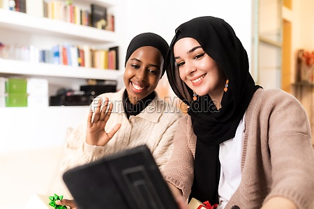 two young muslim women using tablet