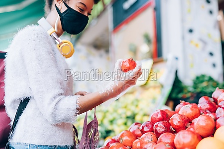 young woman choosing fruit at stall
