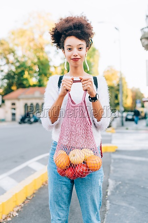 young woman holding fruit in string