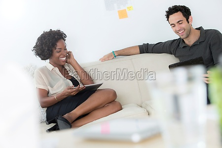 office workers on sofa using digital