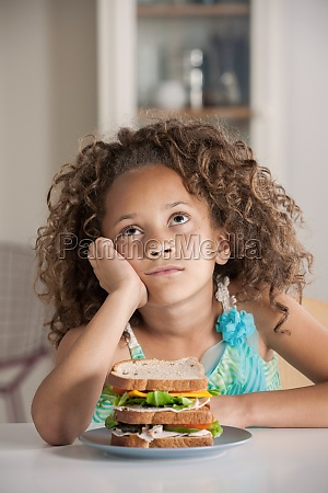 girl staring upwards with sandwich