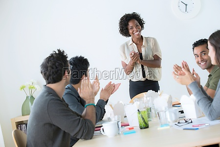 office workers clapping at meeting