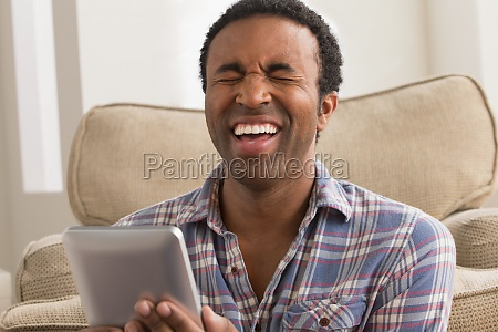 young man with electronic book laughing
