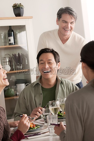 mature friends enjoying meal together