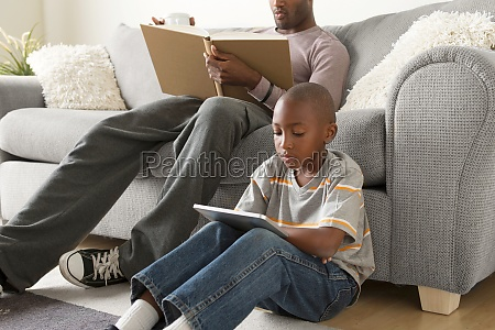 boy sitting on floor using digital