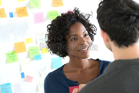 male and female office workers chatting