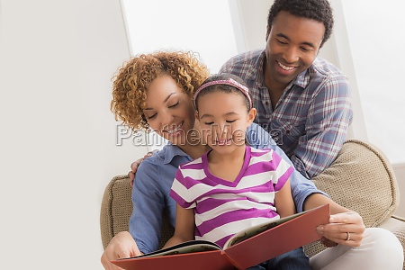 parents with daughter reading book