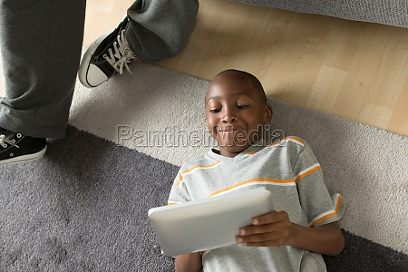boy lying on floor using digital