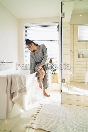 woman in bathrobe preparing soaking tub
