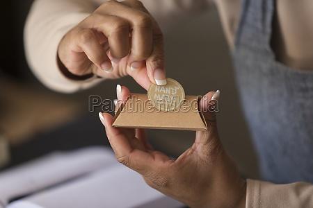 close up female shop owner applying
