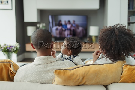 parents and baby daughter watching tv