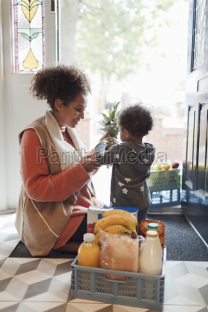 baby daughter helping mother unload grocery
