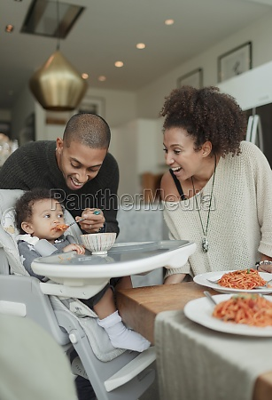 happy couple feeding baby daughter in