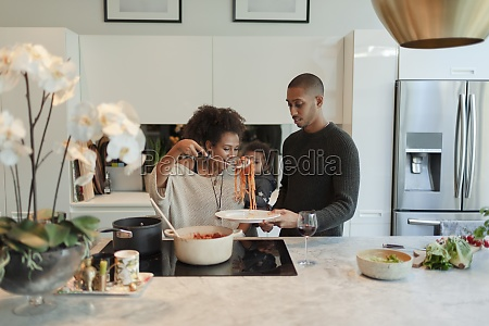 couple with baby daughter cooking spaghetti