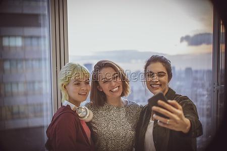 smiling businesswomen taking selfie at highrise