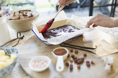 woman baking chocolate brownies in kitchen