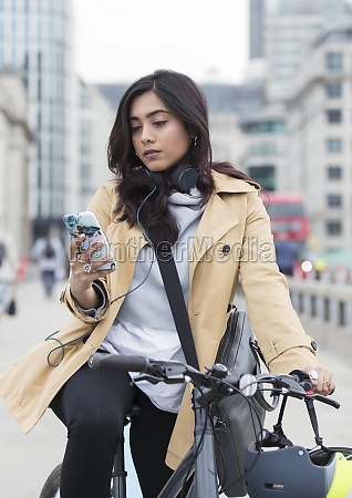 woman on bicycle using smart phone