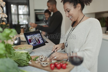 happy woman cooking and video chatting