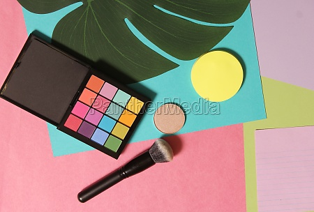cosmetics on paper with tropical leaf