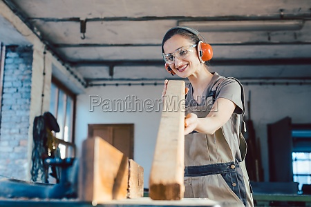 beautiful woman carpenter checking quality of