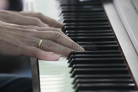 two hands playing on a piano