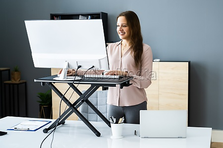 adjustable height desk stand in office
