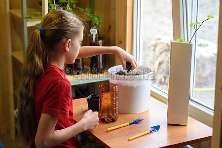 girl pouring soil into a pot