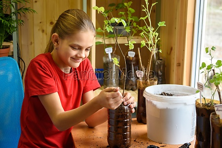 happy girl pours soil into plastic