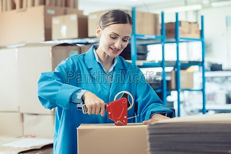 woman in factory warehouse packaging goods