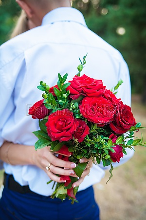 bride holding beautiful bouquet of red