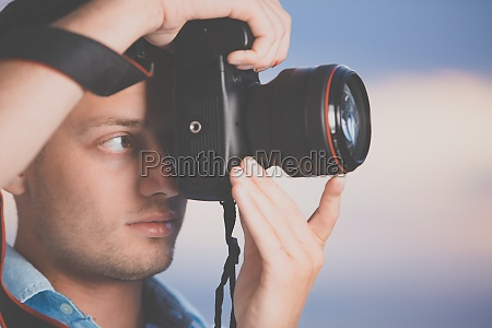 handsome young photographer using his modern