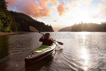 adventurous girl kayaking in the pacific