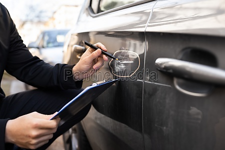 insurance agent or adjuster inspecting car