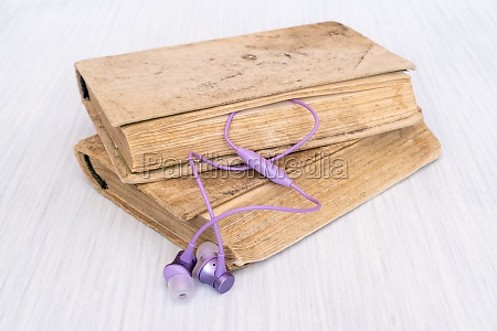 purple earphones and books