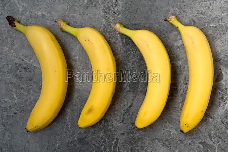 four bananas on the dark stone