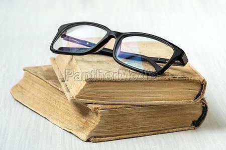 eyeglasses on stacked books