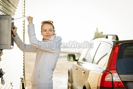 cute woman washing her car in