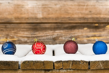four christmas bauble in the snow