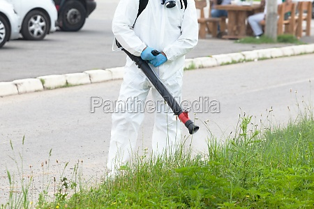 worker in protective suit spray disinfectant