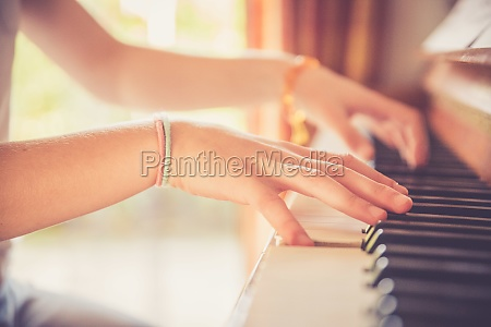 girl is playing piano at home