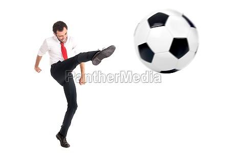 businessman kicking a football