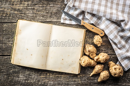 blank cookbook and raw jerusalem artichoke