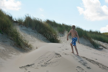 boy runs on a sand dune