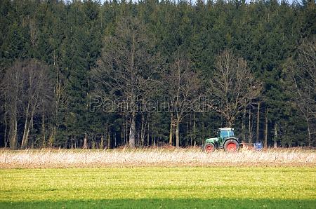 traktor beim ackern vor einem grossen