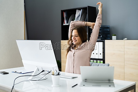woman stretching at office desk
