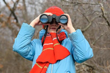 a girl looks through binoculars on